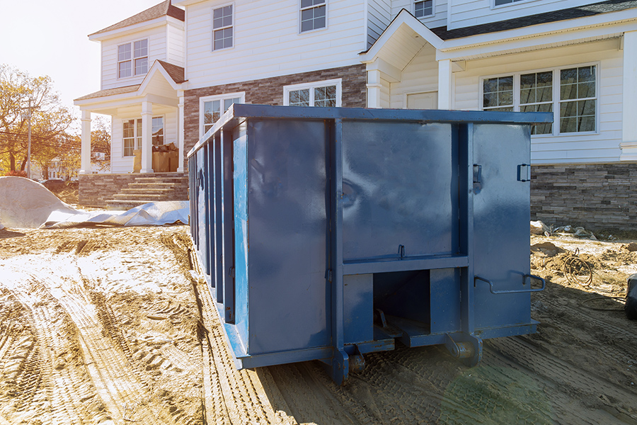 Roll-Off Contractor Insurance - Blue Dumpster in Front of New Home for Waste and Construction Materials at Construction Site
