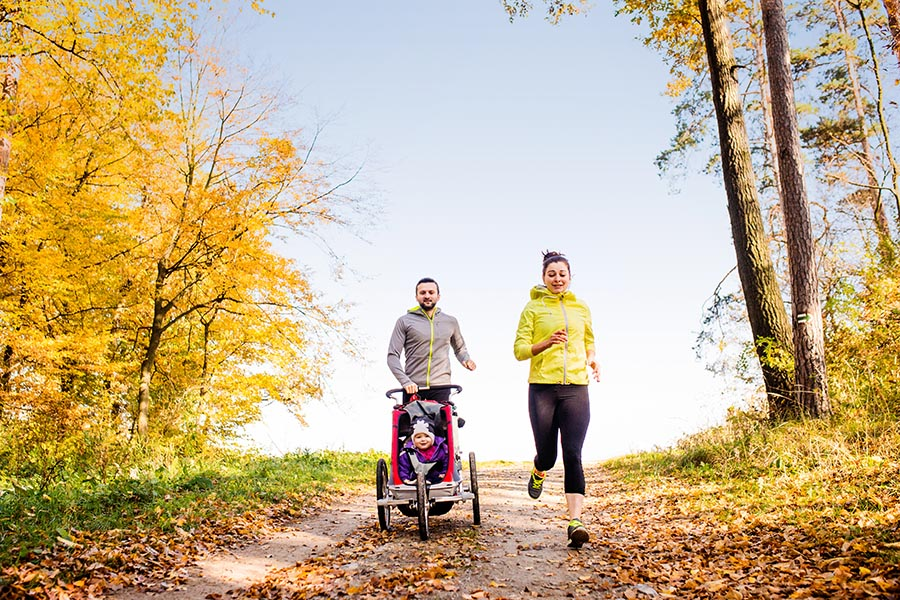 Blog - Parents Jog With Their Baby in a Jogging Stroller, Along a Leaf-Lined Path Through the Woods in the Fall