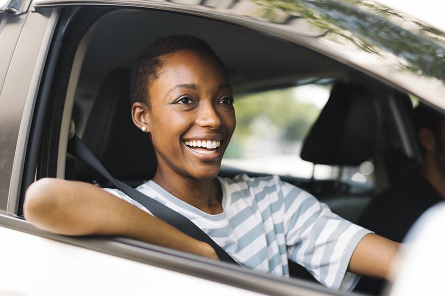 Contact Us - Woman Smiles in the Passenger Seat of a Silver Car, Resting Her Elbow on the Window