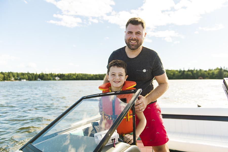 Personal Insurance - Father and Son Stand at the Controls of Their Boat on a Calm Lake, Sun Shining