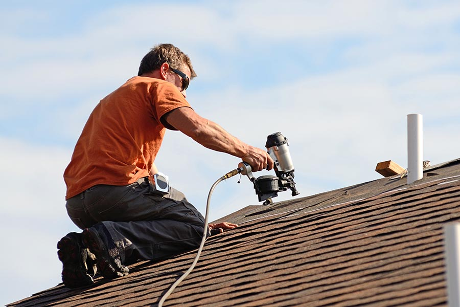 Specialized Business Insurance - Roofer Works on a Sunny Day Using a Nail Gun